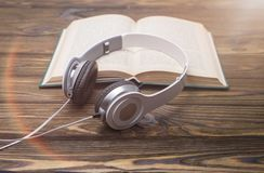 Audio book on the background of a wooden table. Audio book concept. Headphones and old book over wooden table Royalty Free Stock Photography