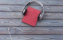 Audio book concept. Headphones and old book over wooden table Royalty Free Stock Photography