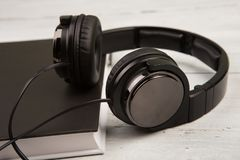 Audio book concept with black book and headphones on white woode. N background Stock Images