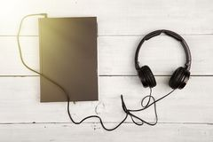Audio book concept with black book and headphones on white woode. N background Royalty Free Stock Images