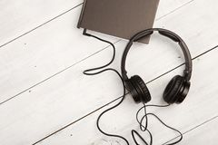 Audio book concept with black book and headphones on white woode. N background Stock Photography