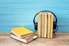 Audio book concept, book and headphones over wooden background. Royalty Free Stock Image
