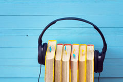 Audio book concept, book and headphones over wooden background. Stock Photography
