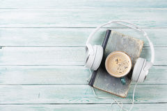 Audio book concept. Headphones, coffee and book Royalty Free Stock Image