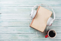 Audio book concept. Headphones, coffee and book. Over wooden table. Top view with space for your text Stock Photos