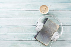 Audio book concept. Headphones, coffee and book Royalty Free Stock Photo