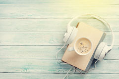 Audio book concept. Headphones, coffee and book Royalty Free Stock Photos