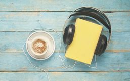 Audio book concept, with book, headphones and coffee, flat lay. Audio book concept, book, headphones and coffee, flat lay on old blue table, vintage image style Stock Photo