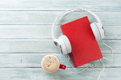 Audio book concept. Headphones, coffee and old book over wooden table. Top view with space for your text Royalty Free Stock Photo