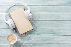Audio book concept. Headphones, coffee and old book over wooden table. Top view with space for your text Royalty Free Stock Photos