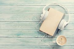 Audio book concept. Headphones, coffee and old book over wooden table. Top view with space for your text. Toned Stock Photography