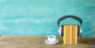 Audio book concept, with book, headphones and cup of coffee, panorama format on grungy background,copy space. Audio book concept, with book, headphones and cup stock image