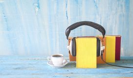 Audio book concept with book, headphones and cup of coffee, panorama format on grungy background, copy space. Audio book concept with book, headphones and cup of stock photography