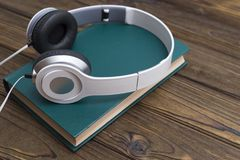 Audio book on the background of a wooden table. Audio book concept. Headphones and old book over wooden table Stock Image