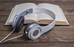 Audio book on a wooden background. Audio book concept. Headphones and old book over wooden table Royalty Free Stock Image