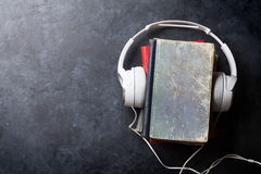 Audio book concept. Headphones and old books over stone table. Top view with space for your text Stock Images