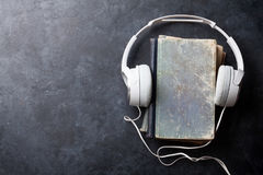 Audio book concept. Headphones and old books over stone table. Top view with space for your text Royalty Free Stock Images