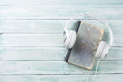 Audio book concept. Headphones and old books over wooden table. Top view with space for your text Stock Images
