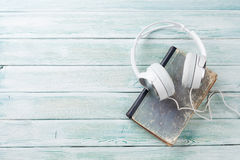 Audio book concept. Headphones and old books over wooden table. Top view with space for your text Stock Photo