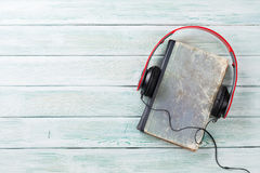 Audio book concept. Headphones and old books over wooden table. Top view with space for your text Stock Photography