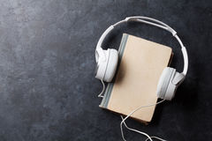 Audio book concept. Headphones and old book over stone table. Top view with space for your text Royalty Free Stock Photography