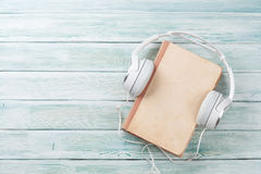 Audio book concept. Headphones and old book over wooden table. Top view with space for your text Stock Image