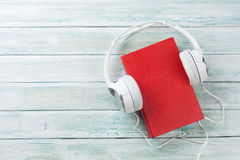 Audio book concept. Headphones and book over wooden table. Top view with space for your text Royalty Free Stock Images