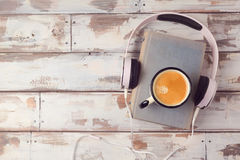 Audio book concept with old book, headphones and coffee cup. View from above. Flat lay Royalty Free Stock Image