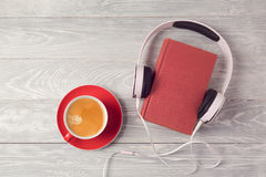 Audio book concept with old book, headphones and coffee cup. View from above. Flat lay Stock Images