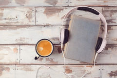 Audio book concept with old book, headphones and coffee cup. View from above. Flat lay Stock Photos