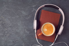 Audio book concept with old book, headphones and coffee cup. View from above. Flat lay Stock Photography