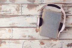 Audio book concept with old book and headphones. View from above. Flat lay Royalty Free Stock Photos