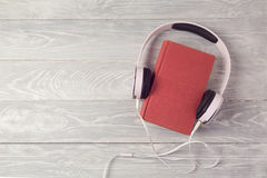 Audio book concept with old book and headphones. View from above. Flat lay Stock Image