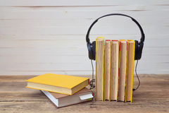 Audio book concept, yellow books and headphones over white backg Stock Images