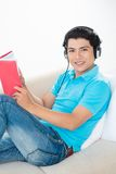 Audio book. Portrait of a young man listening to the audio book indoors Royalty Free Stock Photos