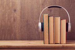Audio books concept with old books and headphones over wooden background Stock Photos
