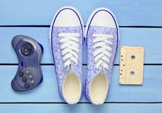 Audio cassette, gamepad, sneakers shoes on a turquoise pastel background. Old-fashioned technologies. Top view. Flat lay.  Stock Photo