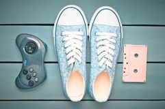 Audio cassette, gamepad, sneakers shoes on a turquoise pastel background. Old-fashioned technologies. Top view. Flat lay. Audio cassette, gamepad, sneakers stock photography