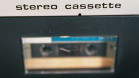 Audio Cassette is inserted into the Deck of the Audio Tape Recorder Playing and Rotates. Macro. Vintage audio cassette tape with a blank label used for sound stock video footage