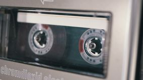Audio Cassette is inserted into the Deck of the Audio Tape Recorder Playing and Rotates. Macro. Vintage transparent audio cassette tape with a blank label used stock video