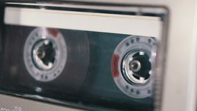 Audio cassette is inserted into the deck of the audio tape recorder playing and rotates. Macro. vintage transparent audio cassette tape with a blank label used stock footage