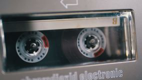 Audio Cassette is inserted into the Deck of the Audio Tape Recorder Playing and Rotates. Macro. Vintage transparent audio cassette tape with a blank label used stock video footage
