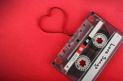 Audio cassette with loose tape shaping a heart Stock Photos