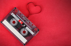 Audio cassette with loose tape shaping a heart Royalty Free Stock Images