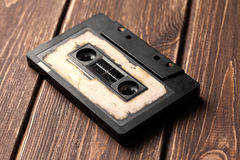 Audio cassette with magnetic tape. On wooden background royalty free stock photo