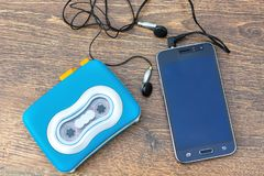 Audio cassette player, blank screen touch phone. Time and technology. Audio cassette player, blank screen touch phone and headset on the background of wooden stock image