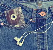 Audio cassette in a pocket of old-fashioned blue jeans and headphones isolated on a white background. royalty free stock image