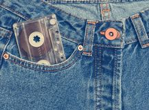 Audio cassette in a pocket of old-fashioned blue jeans. Isolated on a white background stock photos
