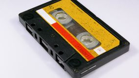 Audio Cassette Rotates on White Background. Vintage Yellow Retro tape cassette with a blank label. Old music. Close-up stock footage