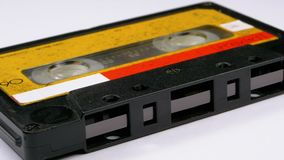 Audio Cassette Rotates on White Background. Vintage Yellow Retro tape cassette with a blank label. Old music. Close-up stock video